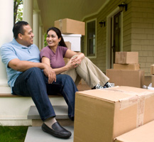 Man and woman sitting on porch with moving boxes