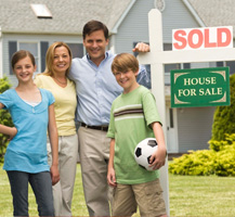 Family standing next to Sold sign