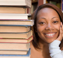 Young woman next to a stack of books